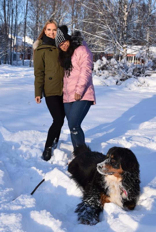 Maija ja Milena seisovat lumihangessa toistensa kainalossa ja hymyilevät. Etualalla Maijan berninpaimenkoira Bella, jonka kuono on lumesta valkoinen.