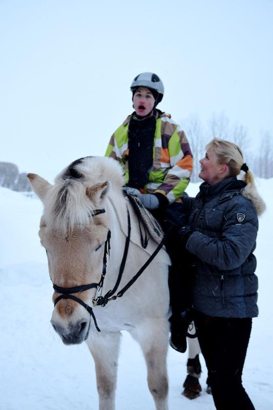 Kuvassa ohjaajansa kuunteluun keskittyvä Jarl-terapiahevonen. Selässä Retu, maassa hevosen vieressä ratsastusterapeutti Miia Vallema.