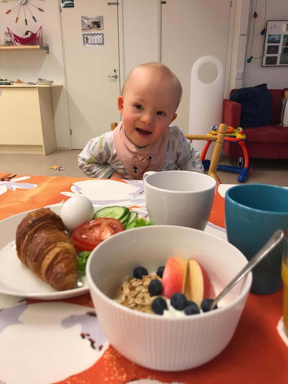 Kuvassa down-taapero ruokapöydän ääressä. Kuvan etualalla aamupalaa: jugurttia ja marjoja, croisanttia, vihanneksia, kananmuna, kahvimukeja.