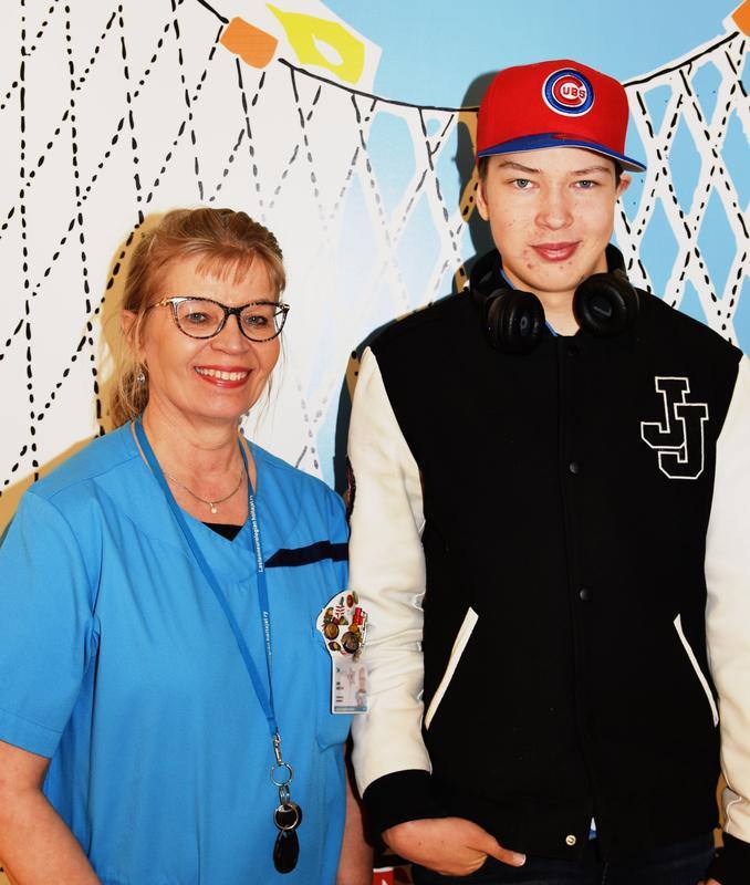 Kuvassa seisovat vasemmalla lastenhoitaja Anne ja vieressä häntä jo melkein päätä pidempi Arttu.