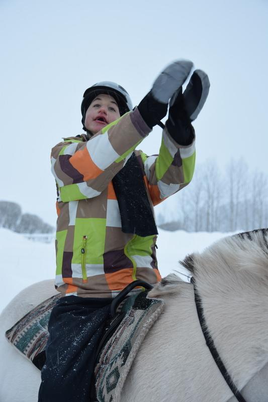 Retu hymyilee iloisesti ja taputtaa käsiään yhteen korkealla ilmassa hevosen selässä istuen.