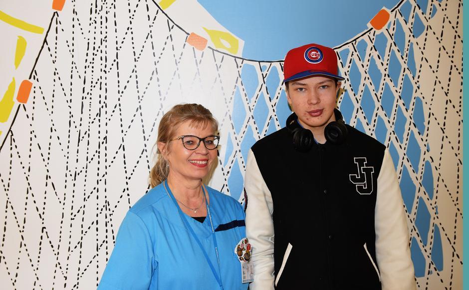 Lastenhoitaja Anne ja Arttu seisovat vierekkäin Uuden Lastensairaalan aulassa. Taustalla muumiaiheinen maalaus.