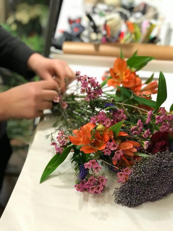 Kukkakauppa Florannan kauppias sitoo Jaakolle värikästä kukkakimppua