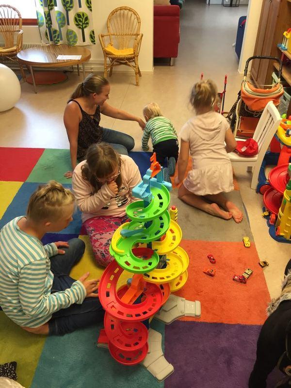 Kuvassa neljä lasta ja äiti istuvat leikkihuoneen lattialla leikkimässä.
