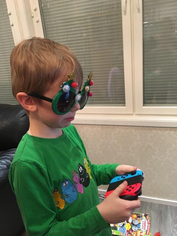 Kuvassa poika pelaa Nintendolla. Hänellä on silmillään hassut lasit.