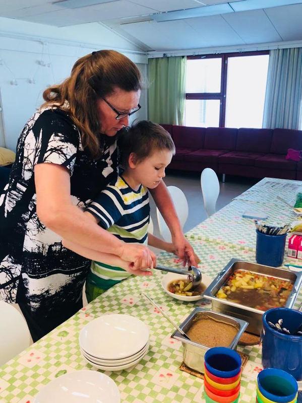 Kuvassa opettaja Eija Virta avustaa oppilastaan pitäen oppilaan käsistä kiinni ja tukien häntä ottamaan itse ruokaa keskellä pöytää olevasta isosta ruoka-astiasta Jaatisen Majan ruokailutilassa.