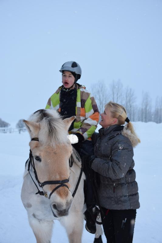 Kuvassa Retu istuu Jarl-norjanvuonohevosen selässä. Hevosen vieressä seisoo ratsastusterapeutti Miia Vallema joka katsoo Retua hymyillen.