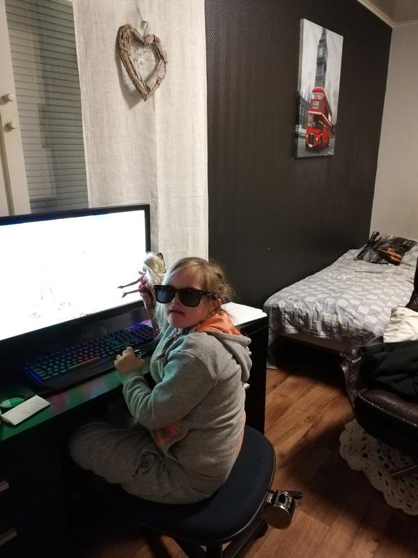 Kuvassa tyttö pelaa tietokoneella mustat lasit silmillään.
