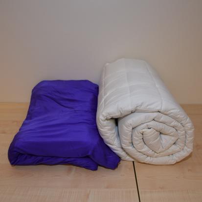 Kuvassa kaksi painopeittoa jotka eivät ulkonäöltään eroa tavallisista peitoista mutta joissa on sisällä painavaa materiaalia.