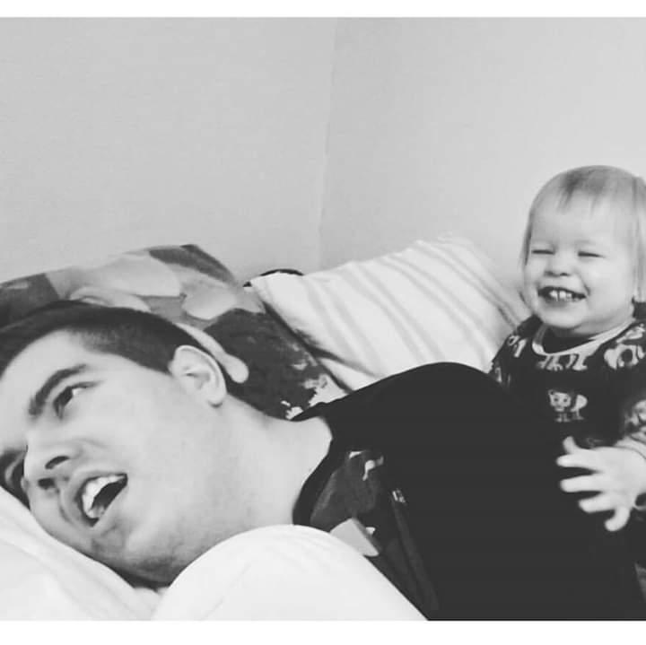 Kuvassa näkyy makuuasennossa oleva nuori mies jonka selän takana nauraa silmät sikkurassa hänen 2-vuotias pikkuveljensä. Pikkuveli pitää isoveljen selästä kiinni kädellään.