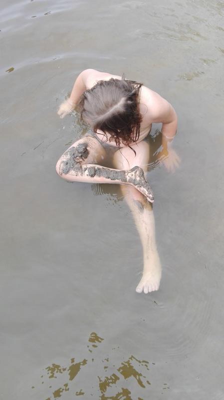 Kuvassa matalassa vedessä istuva tyttö, jonka jalan päällä on kerros mutaa.