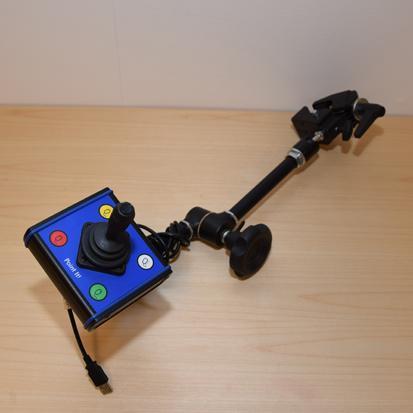 USB-hiiressä on tanko, joka voidaan kiinnittää pyörätuoliin. Tangon päässä on neliö jonka keskellä on joystick ja neljä painiketta.