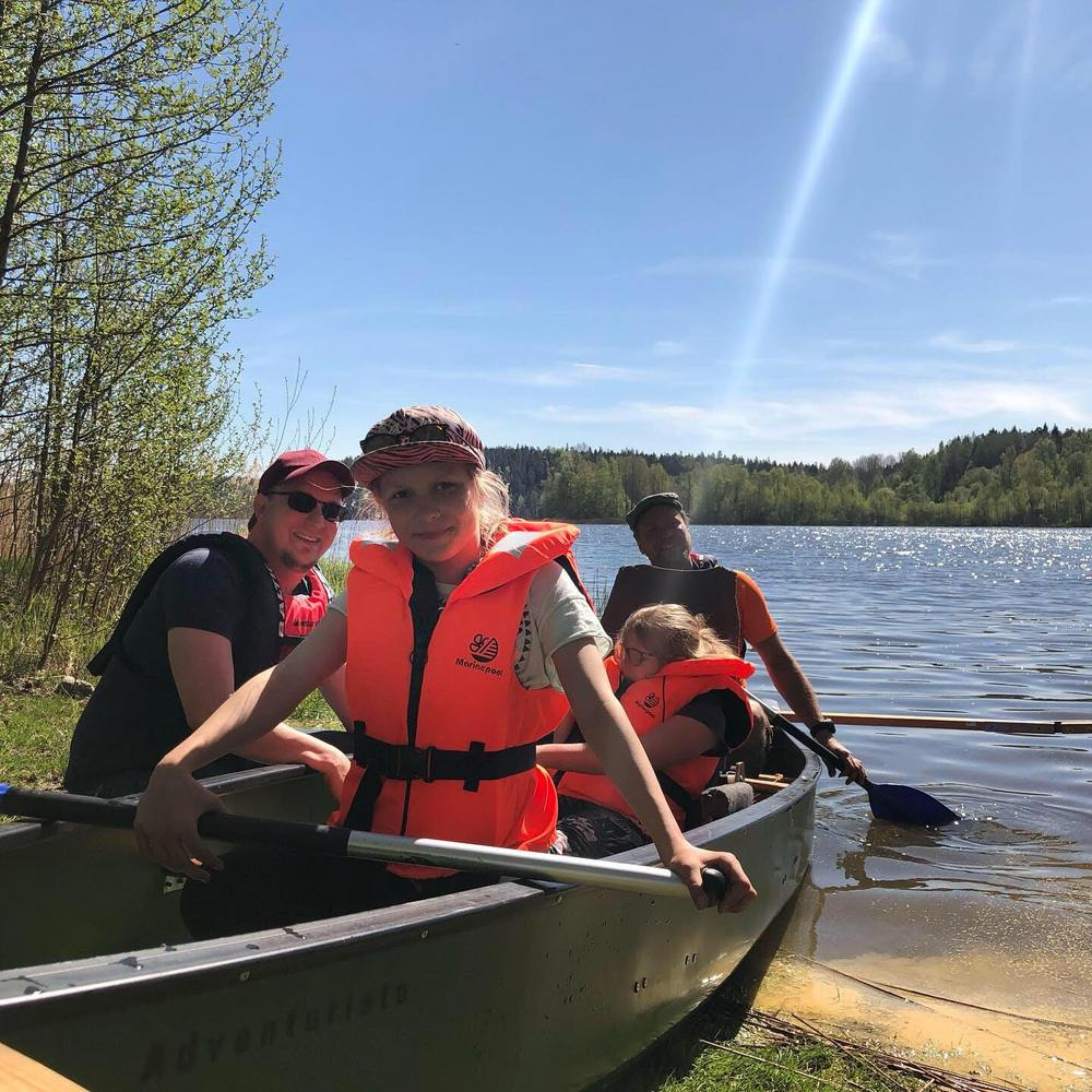 Kuvassa tyttö istuu kanootissa sekä pienempi tyttö ja kaksi avustajaa hänen takanaan.