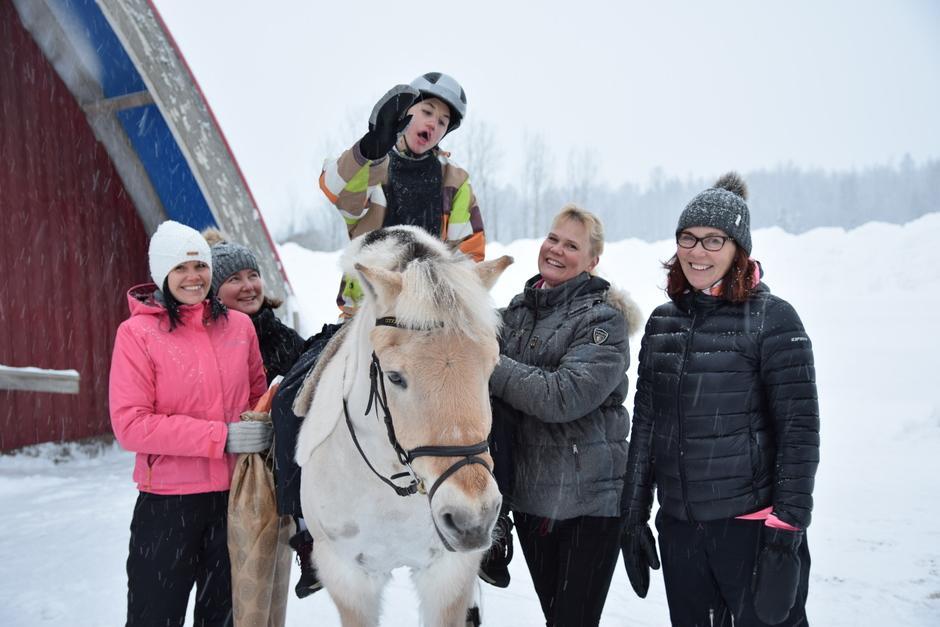 Keskellä lumisessa maisemassa terapiahevosen selässä istuu Retu, joka vilkuttaa. Hevosen vieressä maassa seisovat Sini Kervinen (vas.), koulunkäyntiavustaja Katja Sipari, ratsastusterapeutti Miia Vallema sekä Retun äiti Outi Koivikko.