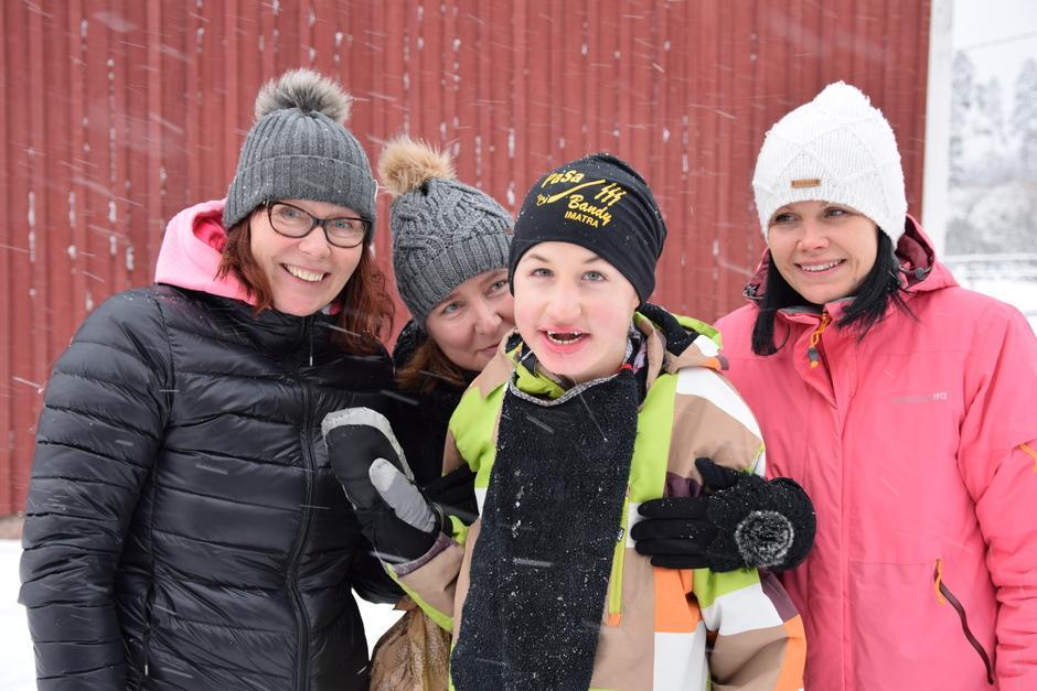 Retun koulunkäyntiavustaja Katja Sipari halaa iloisesti hymyilevää Retua takaapäin, kuvassa mukana myös iltapäivä- ja tilapäishoidon vastaava Sini Kervinen ja Retun äiti Outi Koivikko. Kaikki hymyilevät talvisessa maisemassa lumisateessa.