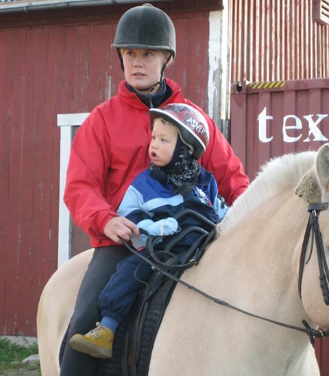 Norjanvuonohevosen selässä istuu ratsastusterapeutti Miia Vallema. Hänen edessään istuu 3-vuotias Retu.