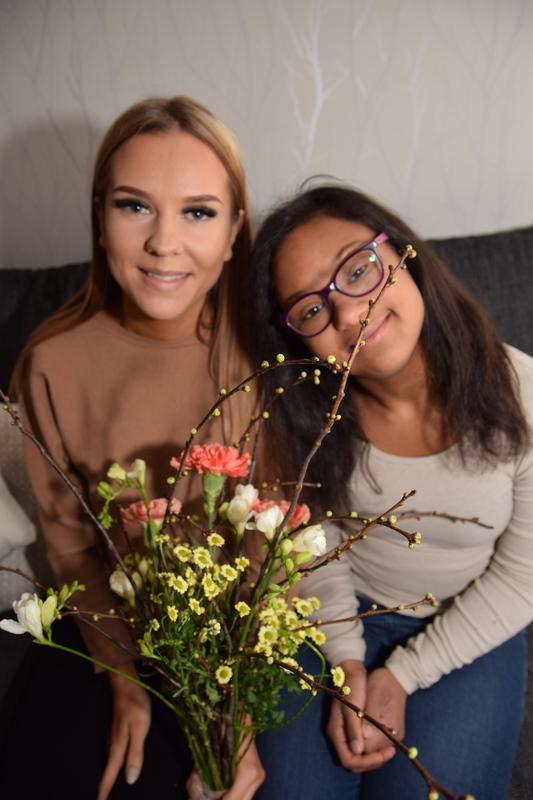 Maija ja Milena istuvat sohvalla kylki kyljessä ja hymyilevät. Milenalla on kädessään kukkakimppu.