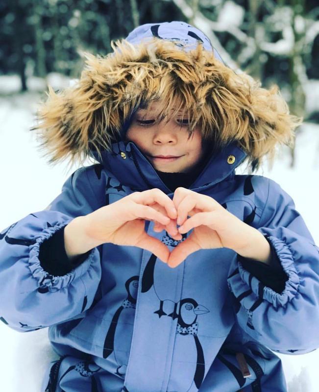 Kuvassa lapsi toppatakissa lumisessa maisemassa muodostaa käsistään sydämen.