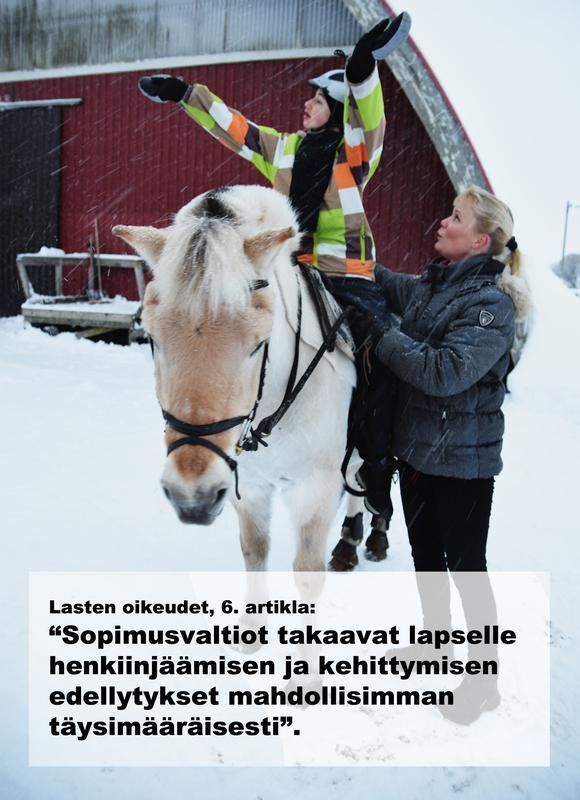 Retu istuu norjanvuonohevosen selässä molemmat kädet nostettuna korkealle ilmaan. Hevosen vieressä ratsastusterapeutti Miia Vallema tukee Retua.