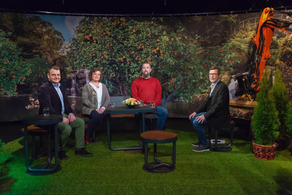 Keskustelijat istuvat puistokalusteilla värikkääksi ja vehreäksi lavastetussa studiossa.