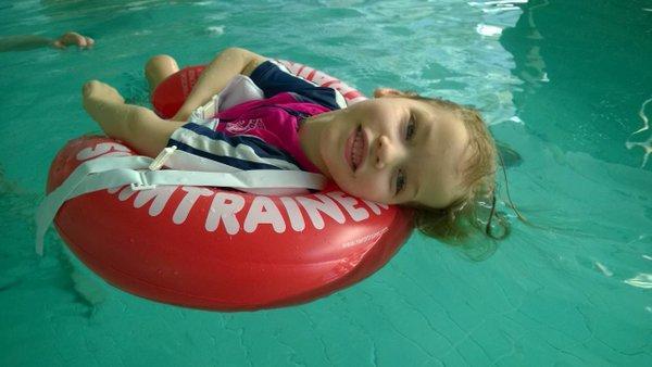 Kuvassa tyttö makaa selällään uimarenkaan päällä uima-altaassa ja hymyilee onnellisen näköisenä.