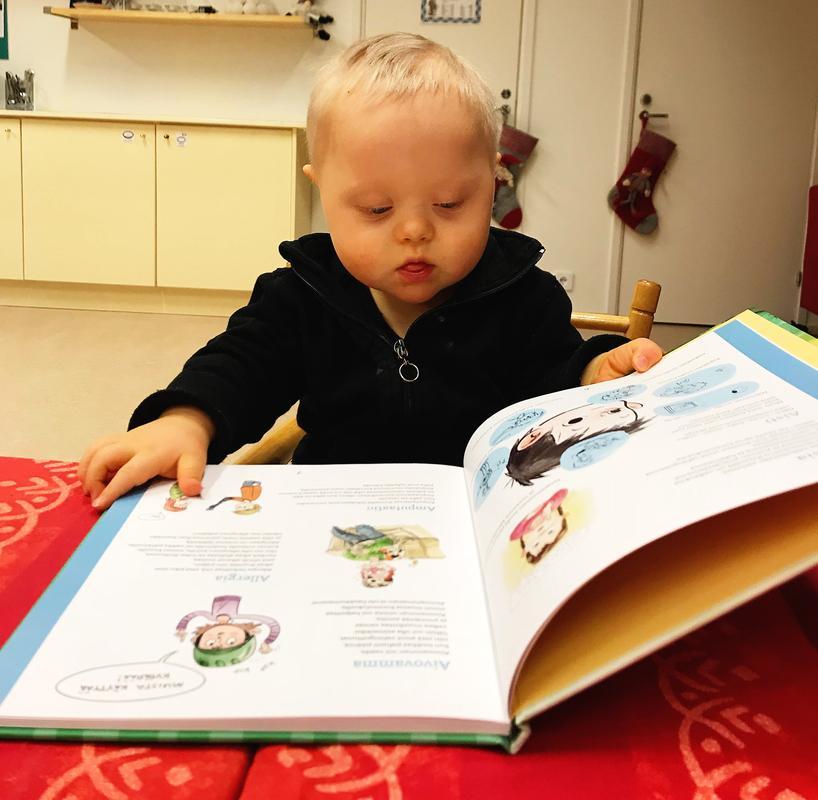 Kuvassa pieni down-poika istuu ruokapöydän ääressä ja selaa lastenkirjaa.