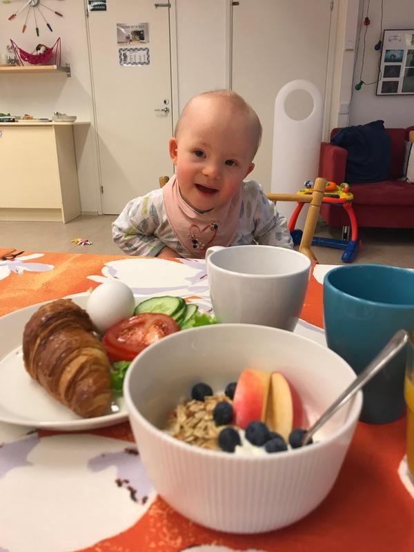 Kuvassa pieni down-tyttö ruokapöydän äärellä Jaatisen Majalla Helsingissä. Pöydälle katettu herkkuja: jugurttia marjoilla ja hedelmillä, croisanttia, kananmunaa, kurkku, tomaattia sekä kahvia.