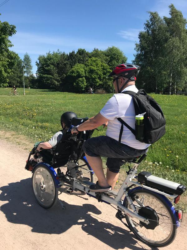 Kuvassa isä polkee yhdistelmäpyörällä Malminkartanossa aurinkoisena kesäpäivänä. Hänen poikansa istuu pyörän etuosassa olevassa istuimessa kyydissä.