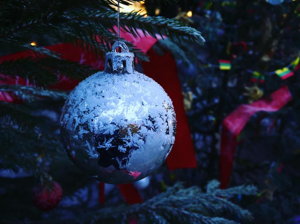 Kuva joulukuusessa roikkuvasta hopeisesta pallokoristeesta.