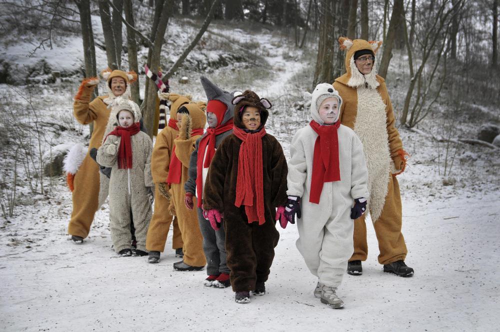 Yhteiskuva eläinasuisista lapsista ja aikuisista, jotka jakavat Joulupolulla piparkakkuja lapsille