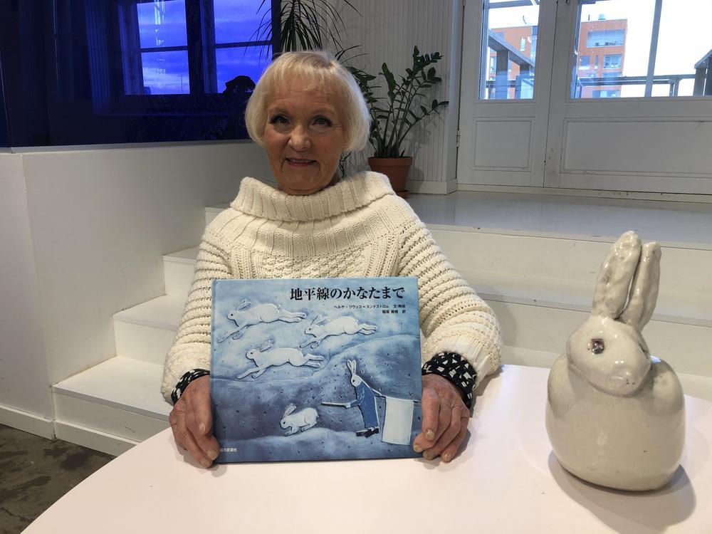 Kuvassa professori Heljä Liukko-Sundström pitelee Jäniksenpoika-teoksen japaninkielistä laitosta vieressään tarinaan liittyvä keraaminen jänisveistos.