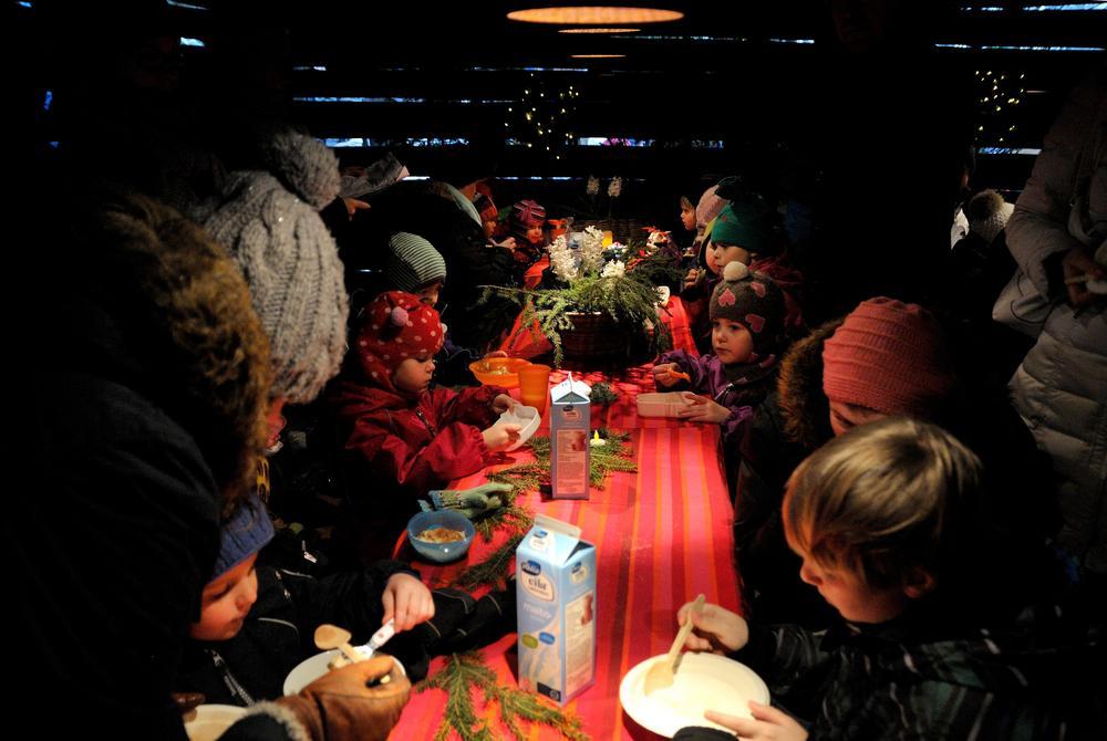 Kuvassa lapsia ja aikuisia istumassa Antin kaffeliiterissä pöydän ääressä. Lapset syövät puuroa.