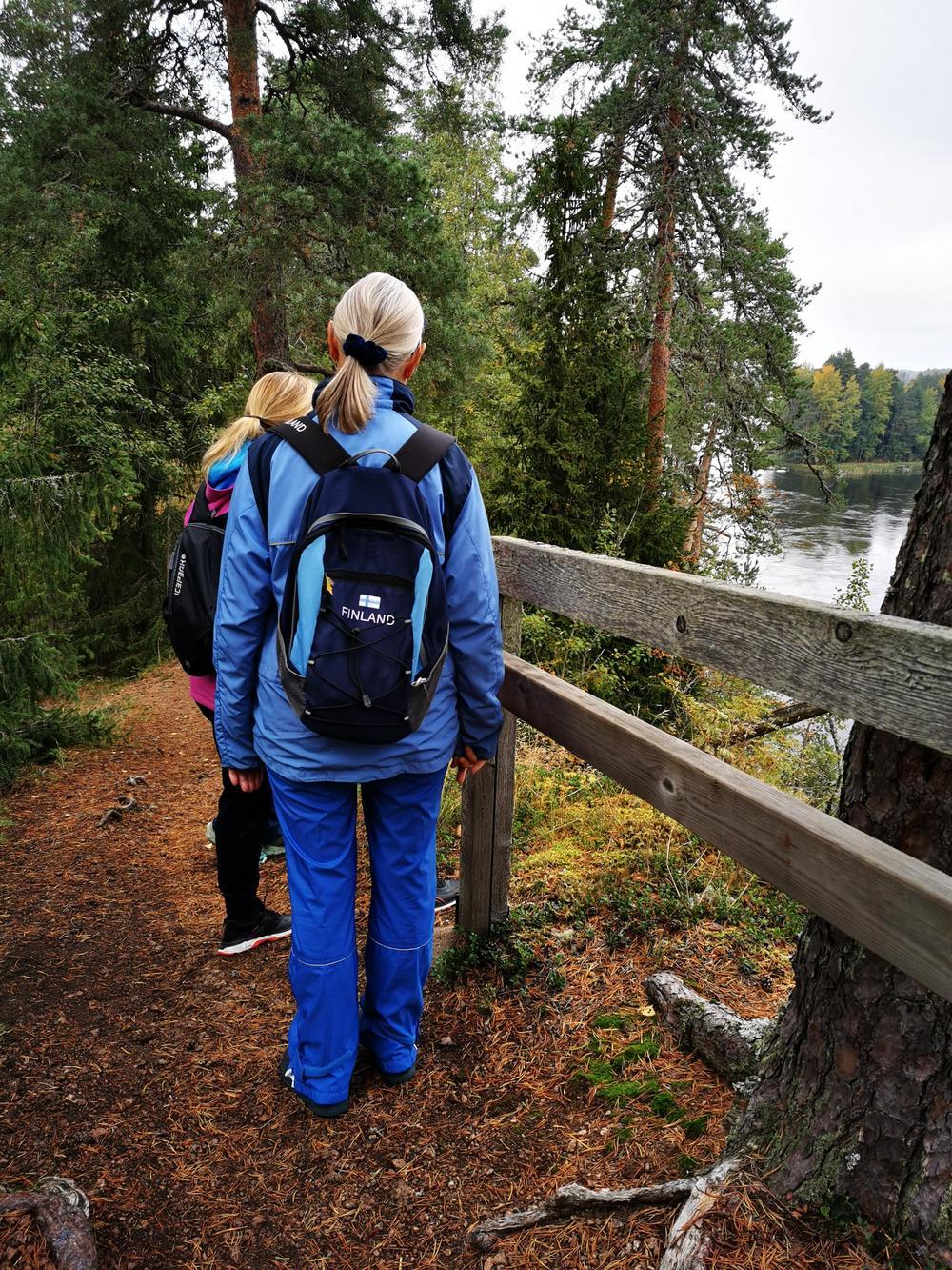 Kaksi naista ulkoiluasuissa katselee Kouvolan Anjalassa sijaitsevan Känkkärän luontopolun varrella Kymijokea kohti.