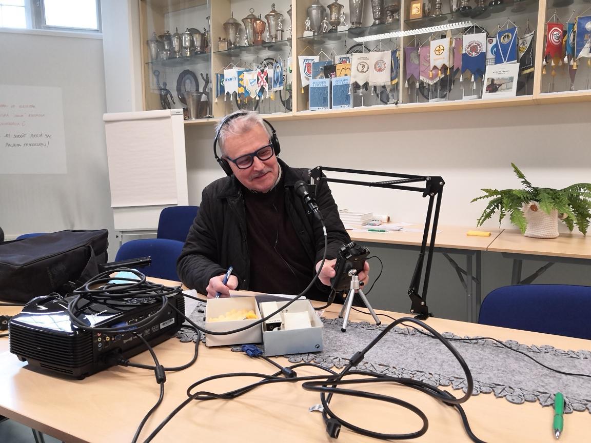 Kuvassa haastatelija Hannu Lehtinen pöydän äärellä kuulokkeet päässä ja eri suuntiin asetettuja haastatteluun tuleville asetettuja mikkejä