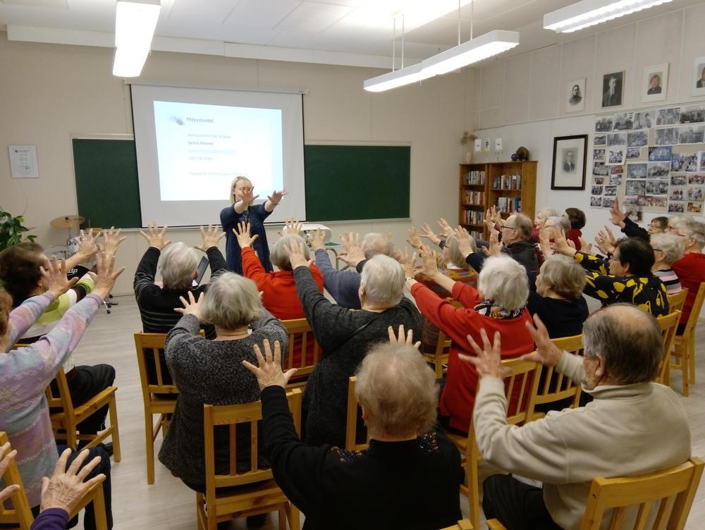 nainen näyttää eteenpäin ojennetun liikkeen käsillä, ja yleisö toistaa saman liikkeen