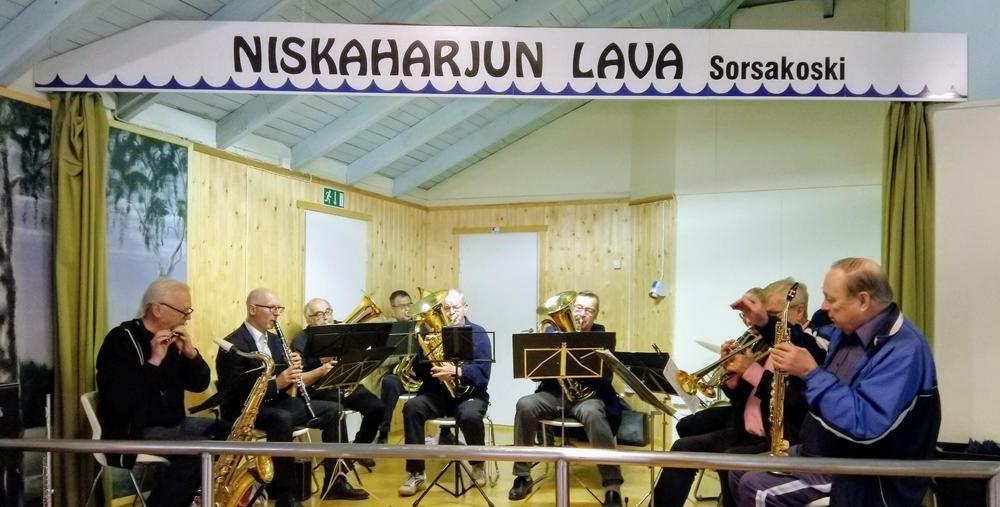 lavalla esiintymässä miesporukka joilla eri soittimia