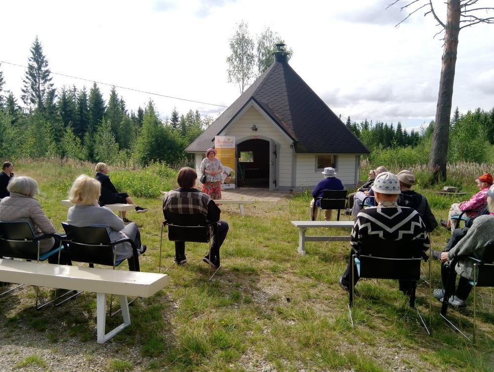 ihmisiä istuu grillikodan edessä, jossa nainen esiintyy