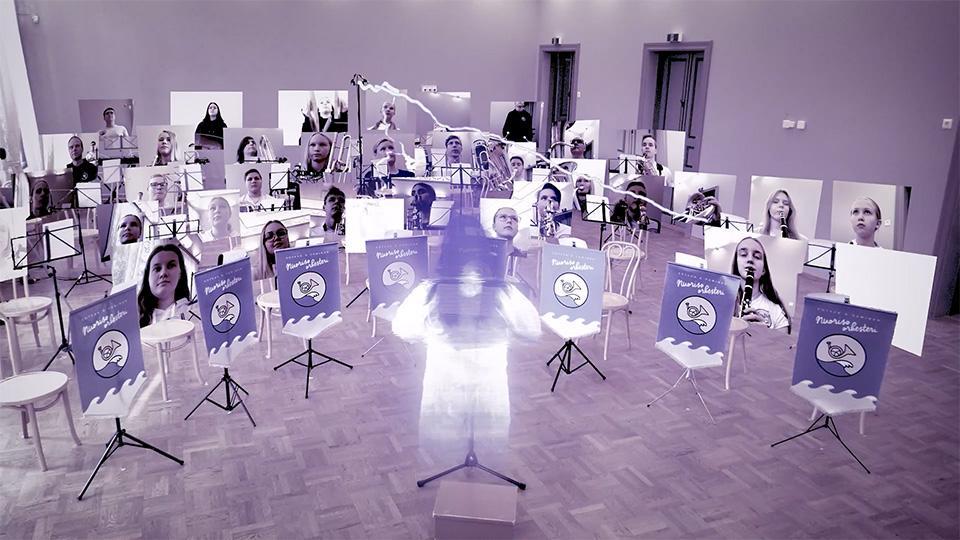 Kuvakaappaus videolta, missä näkyy mosaiikkiorkesteri ja kapellimestarin hologrammi.