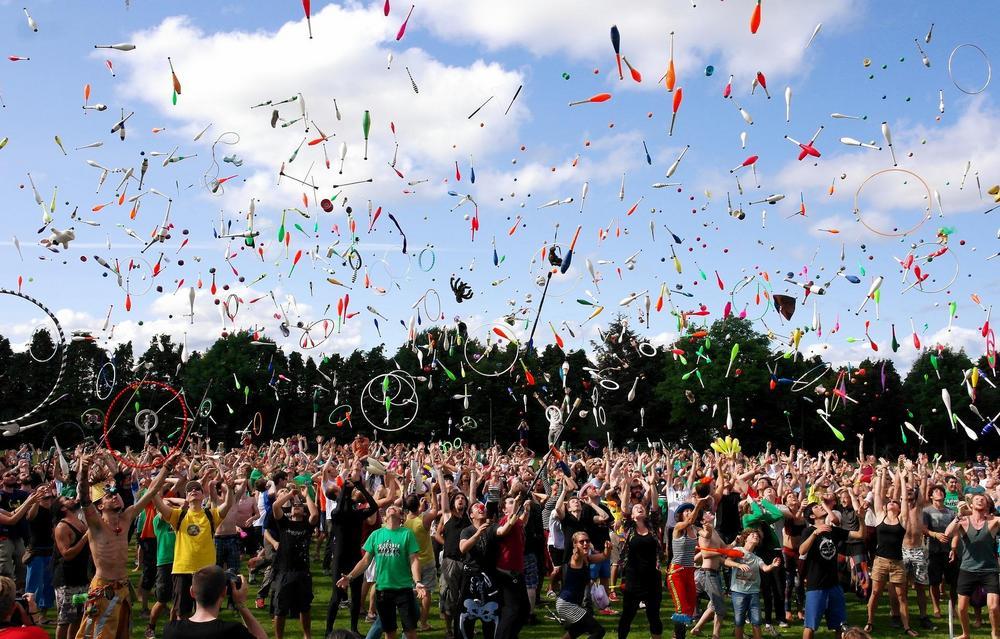 Paljon nuoria on kokoontuneena yhteen. Nuoret heittelevät keiloja ja muita sirkusvälineitä ilmaan. Taivas on puolipilvinen.