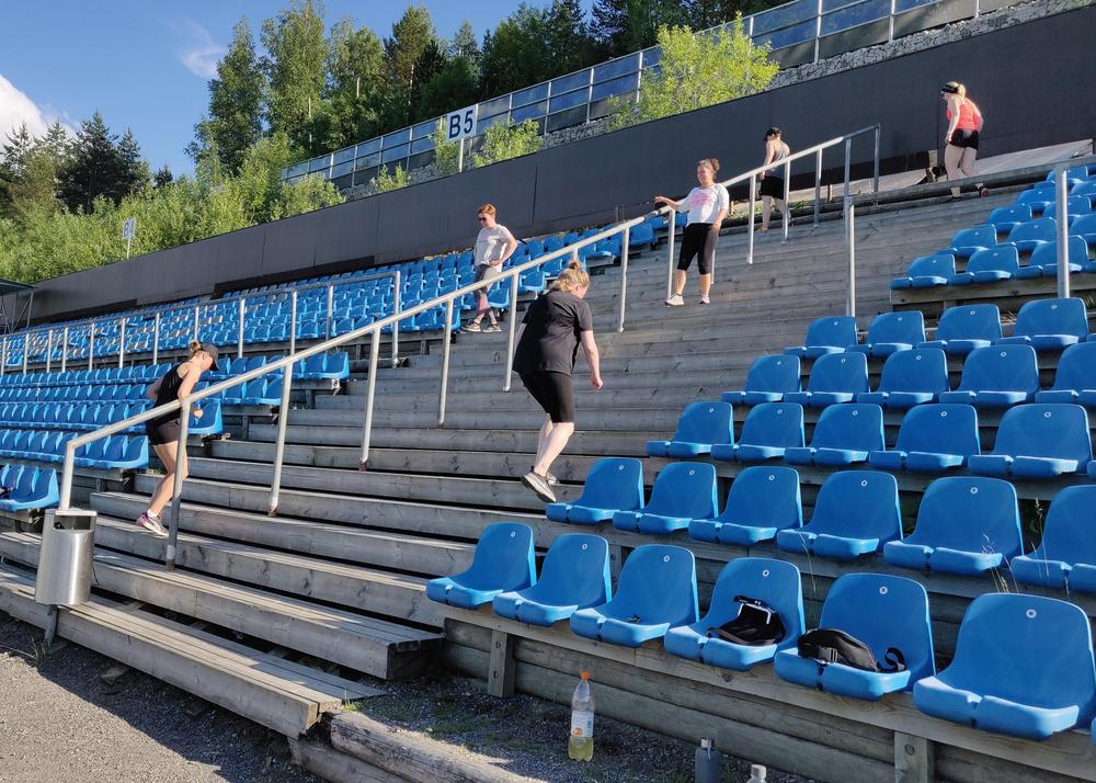 Katsomo, jossa henkilöitä kiipeää ylös portaita ja laskeutuu alas.