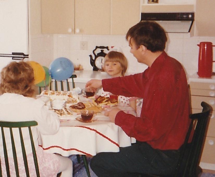 Pyöreän kahvipöydän ympärillä istuu kaksi lasta ja punaiseen paitaan pukeutunut isä.