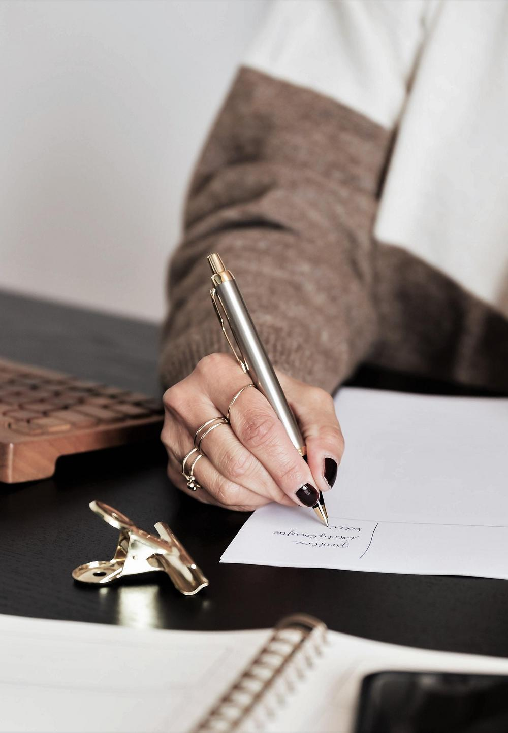 Naisen käsi, joka kirjoittaa mustekynällä paperille. Pöydällä näkyy osittain myös kalenteri, näppäimistö ja puhelin.