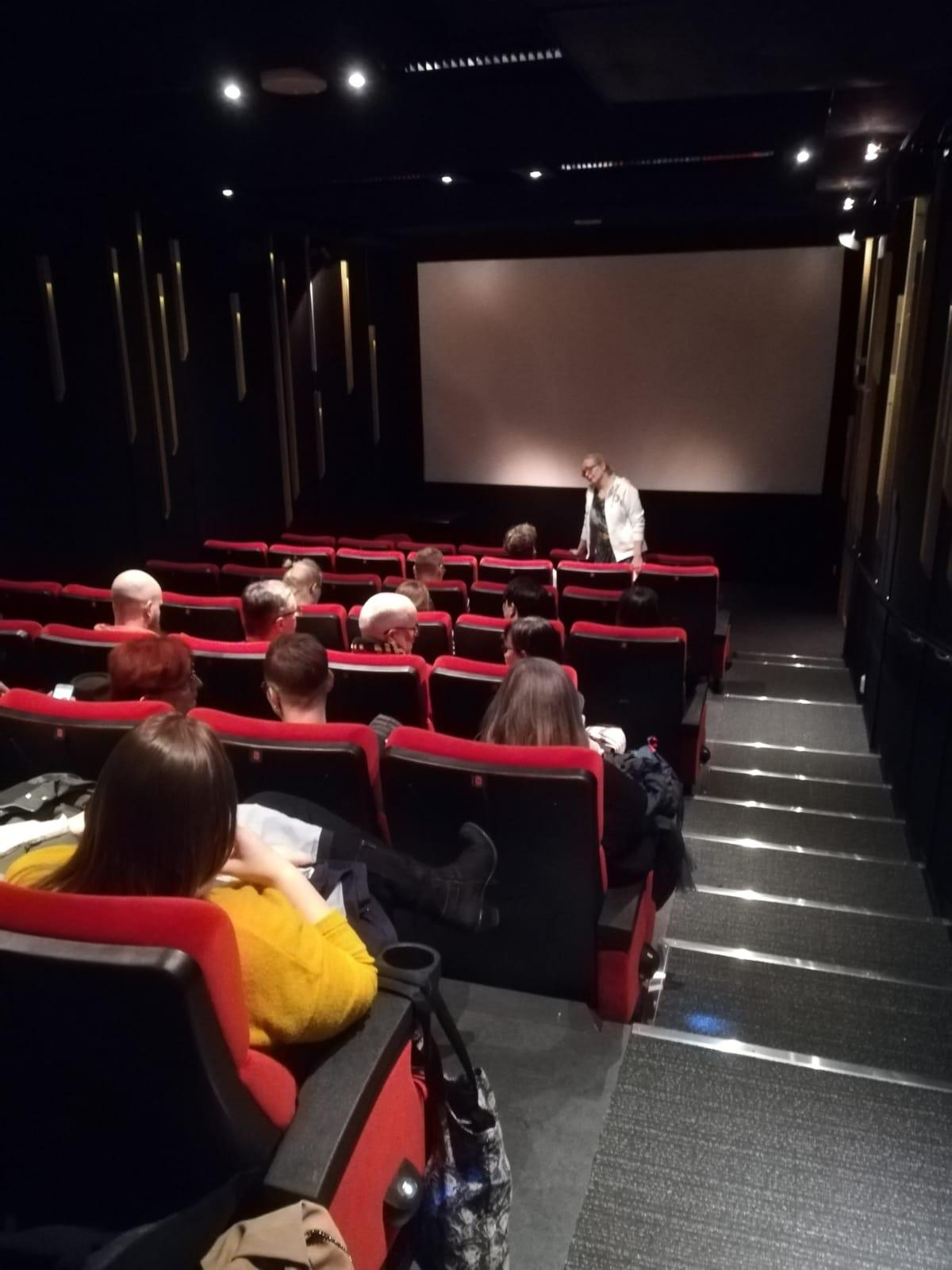 Huoman toiminnanjohtaja Sanna puhumassa elokuvateatterin valkokankaan edessä punaisilla penkeillä istuvalle yleisölle.