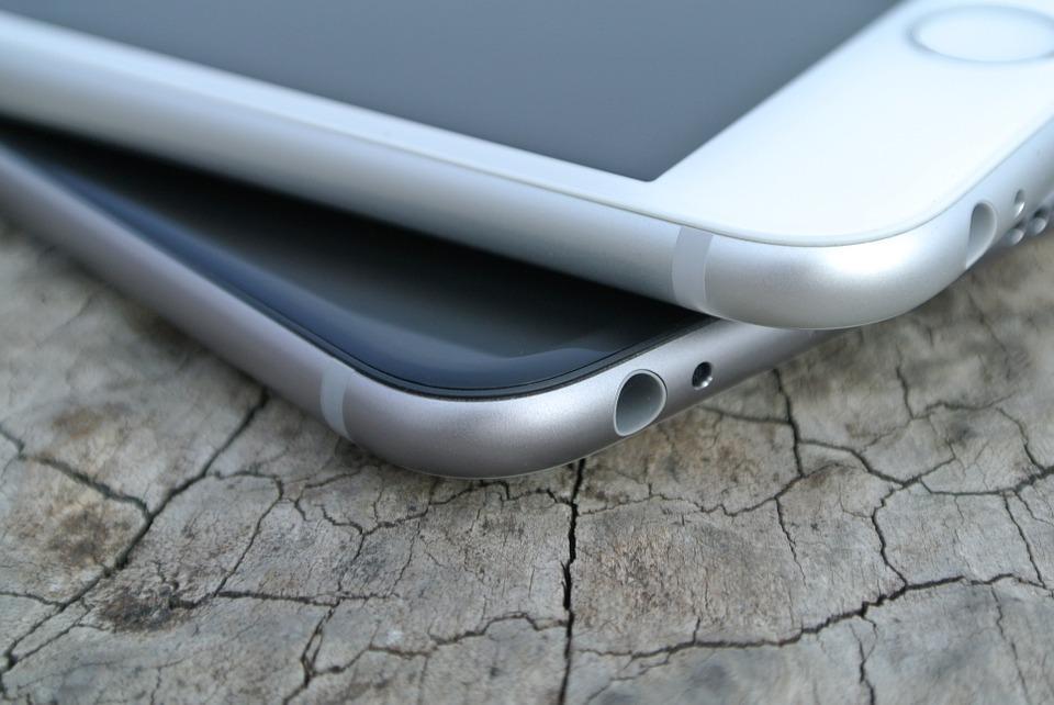 Kaksi älypuhelinta on päälekkäin puisella pinnalla.