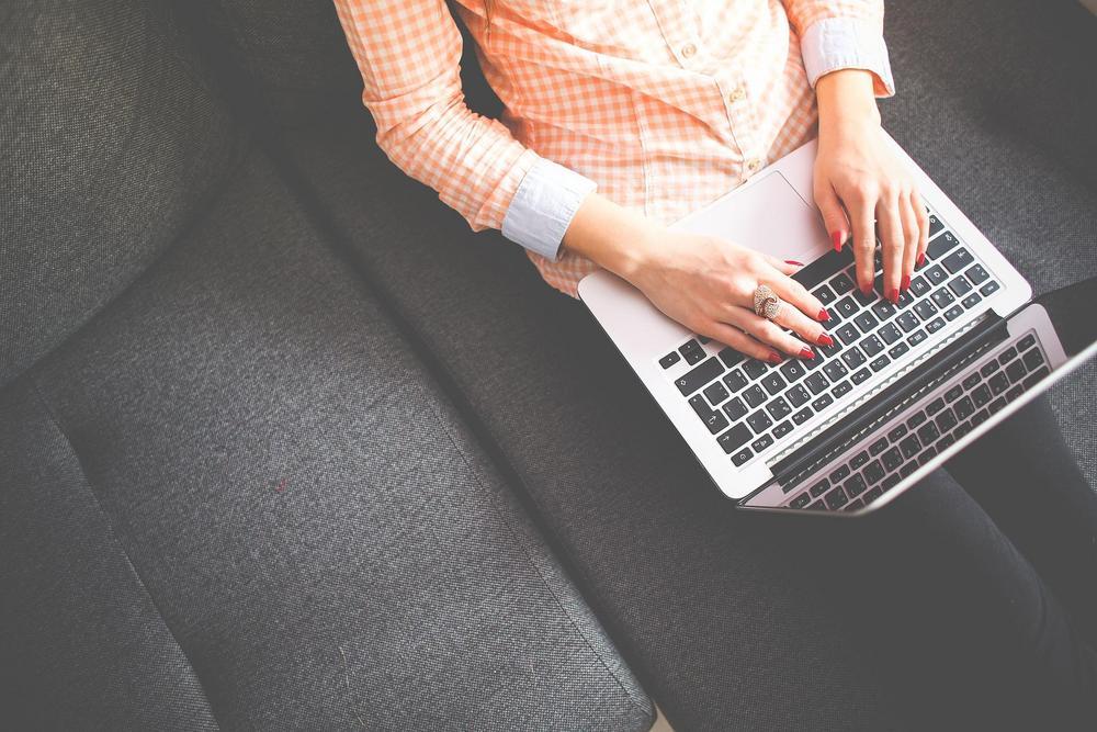 Kuvituskuva. Nainen istuu sohvalla ja kirjoittaa tietokoneella.