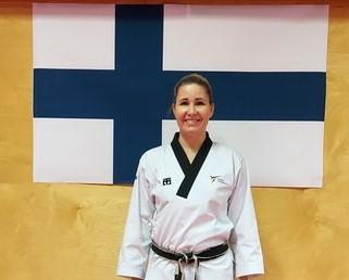 Nainen liikesarja-asussa seisomassa Suomen lipun edessä