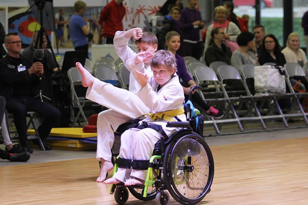 Kaksi pyörätuolissa istuvaa harrastajaa esittämässä liikesarjaa.