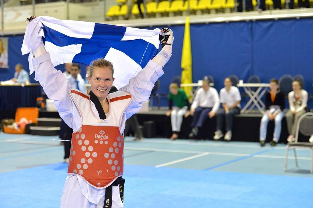 Vaalehiuksinen, hymyilevä, punaiseen taekwondopanssariin pukeutunut nainen kannattelee Suomen lippua päänsä yläpuolella kilpailualueella