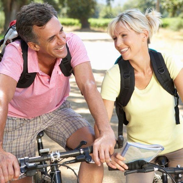 Kuvassa keski-ikäiset mies ja nainen ovat pysähtyneet pyörillä. Molemmat nauravat.