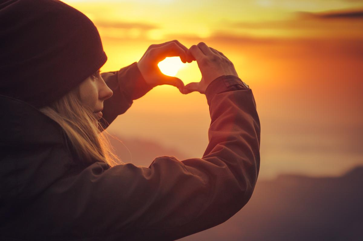Kuvassa nuori nainen muodostaa käsillään sydänmerkin, taustalla aurinko laskee.